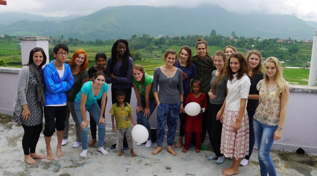 Teenage volunteers doing work with children in Nepal, take a photo with children.